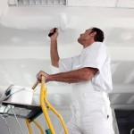 Tradesman painting a ceiling